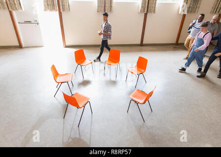 Men arriving, approaching chairs in circle in community center - Stock Image