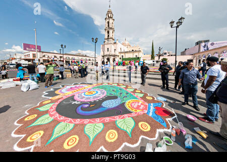 A giant floral carpet decorates the town square in front of the Parroquia San Miguel Archangel church in the central Mexican town of Uriangato, Guanajuato. Every year residents create giant floral carpets made from colored sawdust and decorated with flowers during the 8th Night Celebration marking the end of the Feast of St Michael. Uriangato became an international sensation after wowing Brussels with their floral carpet displayed at the Brussels Grand-Place during the Belgium Floral Carpet festival. - Stock Image