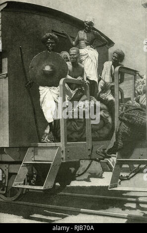 Hadendoa (Hadendowa) men, belonging to a nomadic tribe of cattle grazers in the Sudan area (then part of the British Empire), East Central Africa, riding on a train. - Stock Image