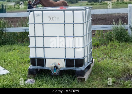 Single water container on skid on farm used for watering livestock - Stock Image