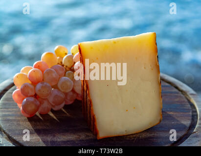 Spanish goat milk cheese with paprika coating and ripe pink table grapes close up - Stock Image
