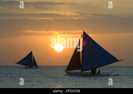 Sailboats at sunset off of White Beach in Boracay, Philippines. - Stock Image