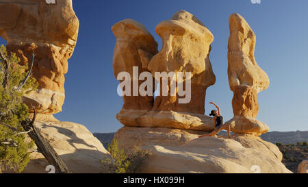 Low angle view of woman practicing yoga and meditating on rock formations in remote desert landscape under clear - Stock Image