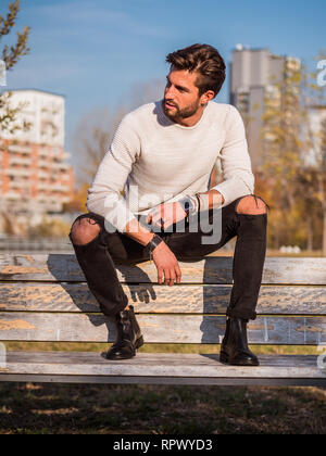 One handsome man in city park, sitting - Stock Image