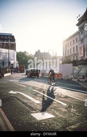 A man cycles through a road near Victoria railway station in the city of London, United Kingdom. - Stock Image