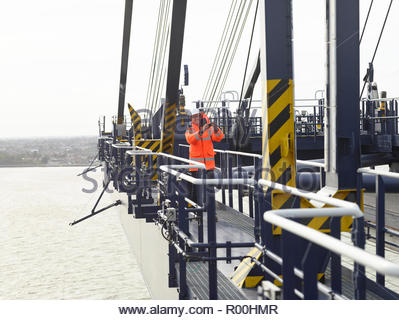 Smiling worker with reflective jacket on dock crane - Stock Image