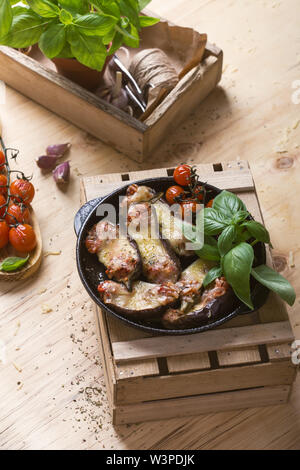 Baked eggplant stuffed with mozzarella cheese and tomatoes, rural table, close up, selective focus - Stock Image