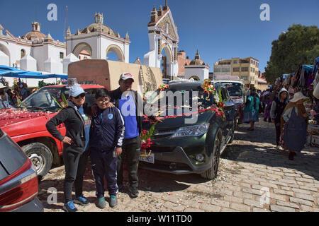 Family having their car blessed, a unique ritual at the Basílica de Nuestra Señora in Copacabana, Bolivia - Stock Image