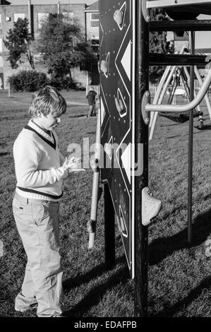 Boy preparing to climb a wall in a playground in Daventry, Northamptonshire during the winter - Stock Image