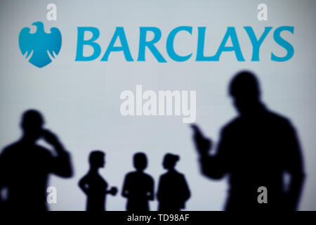The Barclays Bank logo is seen on an LED screen in the background while a silhouetted person uses a smartphone in the foreground (Editorial use only) - Stock Image