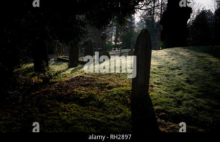 Cemetery Graveyard with tombstones in early morning light - Stock Image