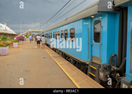 Passenger stretch their legs while the Premier Classe train bound for Cape Town makes a  stop in unkown station, Free State South Africa - - Stock Image