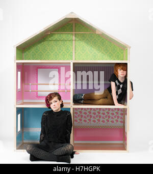 Teen girl and school boy with a giant doll house - Stock Image