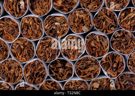 A pile of tobacco cigarettes stacked. - Stock Image