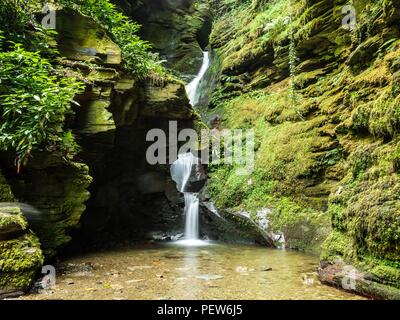 A waterfall through a hole in the rock at St Nectan's Glen in Cornwall - Stock Image