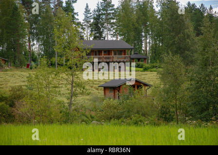 two-storey wooden house and a bath in a picturesque forest. Finland - Stock Image