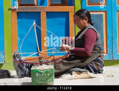 Older Loba woman spinning Himalayan sheep wool, Lo Manthang, Upper Mustang region, Nepal. - Stock Image