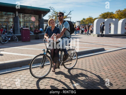 Couple riding a bike in Museumsplaiun near I amsterdam sign - Stock Image