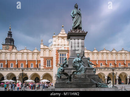 City landmarks Adam Mickiewicz bronze monument and Sukiennice (Cloth Hall) in Old Town, Krakow, Poland. - Stock Image