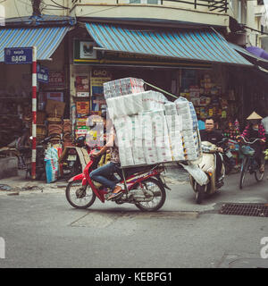 A trader transports his wares on a moped through the busy streets of Hanoi's Old Quarter - Stock Image