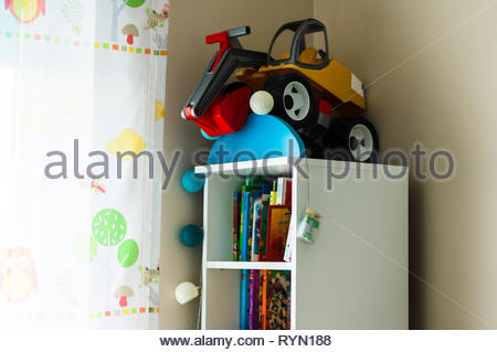 Poznan, Poland - November 18, 2018: White bookshelf with plastic toy excavator on the top in a child room. - Stock Image