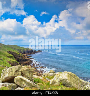 Rocky coastline at Lands End, with the famous Longships Lighthouse out to sea. - Stock Image