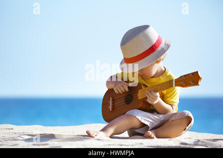 Little boy plays guitar ukulele at sea beach - Stock Image