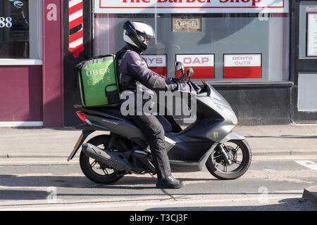 An Uber Eats delivery rider - part of the growing gig economy - on a moped in Worcester, UK - Stock Image