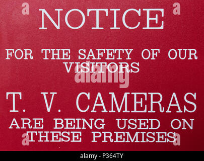 Red and white sign stating: NOTICEFOR THE SAFETY OF OUR VISITORST.V. CAMERAS ARE BEING USED ON THESE PREMISES - Stock Image