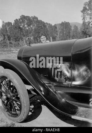 A young woman peeks over the hood of a period automobile, ca. 1928. - Stock Image