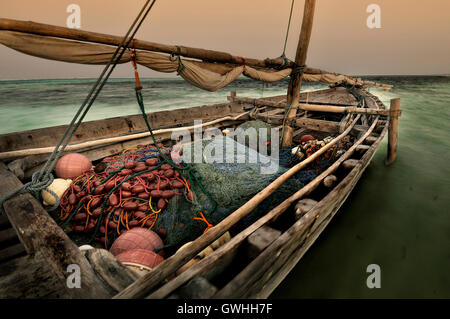 An old wooden fishing boat with nets on the ocean at sunset. - Stock Image