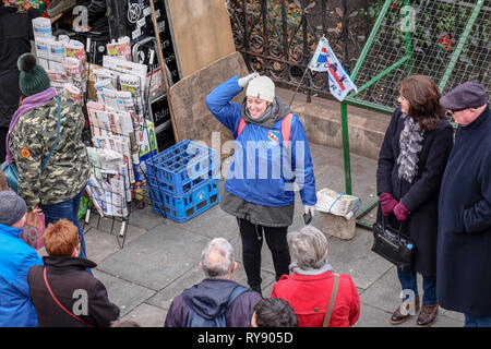 A young female tour guide marked by a talks to a group of older tourists in the West End of London, England - Stock Image