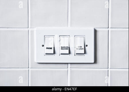 Switches for home appliances against a tiled wall - Stock Image