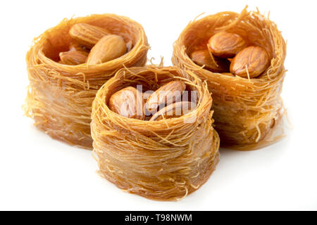 Bird nest baklava with almonds on a white background - Stock Image