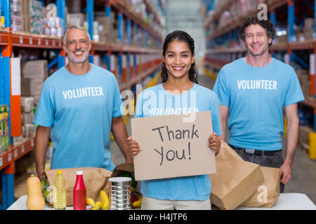 Happy colleagues holding sign boards with thank you message - Stock Image
