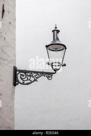 Elegant and simple black corner wall lantern mounted against a white wall in Lucerne, Switzerland. - Stock Image