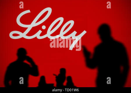 The Eli Lilly logo is seen on an LED screen in the background while a silhouetted person uses a smartphone in the foreground (Editorial use only) - Stock Image