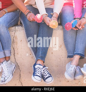 Close up unrecognizable group of women legs with young sneakers shoes and little cocktail umbrella for summer friendship concept together sitting on a - Stock Image