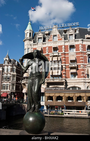 Hotel Europe, canal , sculpture, canal boat , Restaurant Exelsior , Terasse, Amsterdam, Netherlands - Stock Image