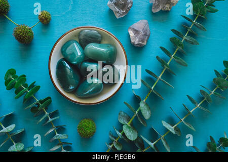 Green Aventurine with Quartz and Eucalyptus on Turquoise Table - Stock Image