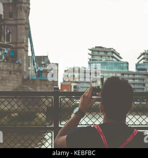 A tourist takes a photo of Tower Bridge on their mobile phone - Stock Image