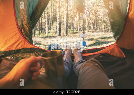 outdoor adventure tourism - man laying in tent with cup of tea - Stock Image