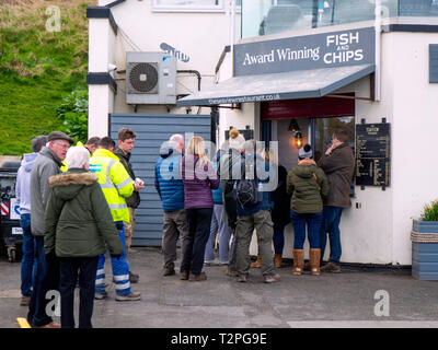 People queuing to buy award winning  Fish and Chips at the Seaview Cafe Restaurant on the sea front at Saltburn - Stock Image