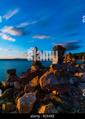 Stack of rocks on beach rocky scenery featuring warm sunset light low view long exposure smooth blurring clouds - Stock Image