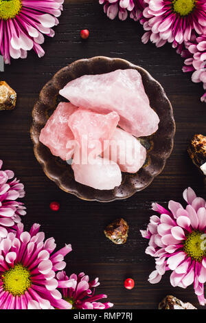 Rough Rose Quartz Crystals with Garnet and Pink Mums on Dark Table - Stock Image