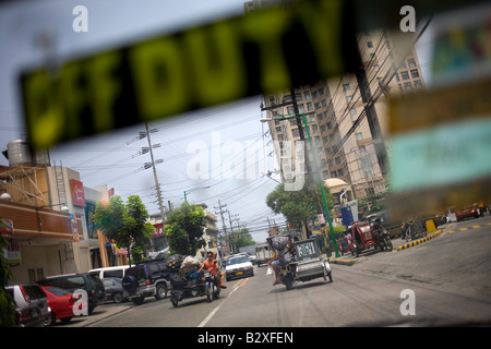 Manila traffic viewed through the windshield of a taxi cab in Manila, Philippines. - Stock Image