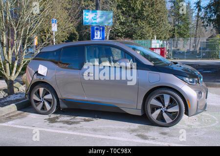 Electric car charging at charging station. - Stock Image