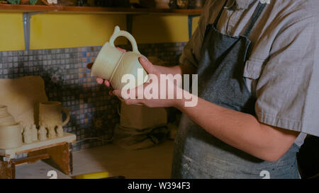 Professional male potter examining jug in workshop - Stock Image
