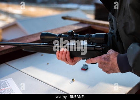 A man holds a gun for target practice and hunting in Pennsylvania, United States - Stock Image