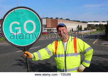 Workman holding a green go sign and smiling on a sunny day - Stock Image